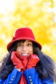 stock photo of shivering  - Happy woman in warm clothes shivering on cold autumn day in park - JPG