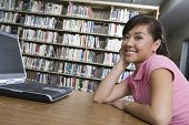 stock photo of shelving unit  - Female university student with laptop in library - JPG