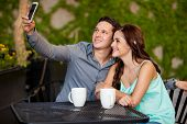 stock photo of two women taking cell phone  - Young attractive couple taking a photo with a cell phone during their first date at a cafe - JPG
