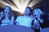 foto of watching movie  - Young people screaming while watching horror movie in the theatre - JPG