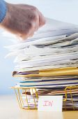 picture of picking tray  - Business image of a male hand with blue shirt cuff visible adding or removing document from tall pile in overflowing office In tray - JPG