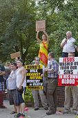 People With Clashing Beliefs Hold Signs At The Bele Chere Festival In Asheville, July 26, 2013