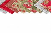 foto of quilt  - Quilting fabrics in different colors and patterns over white with copy space - JPG