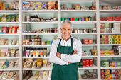 stock photo of supermarket  - Portrait of happy senior male owner standing arms crossed against shelves in supermarket - JPG