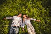 stock photo of lie  - couple in love lying on green grass - JPG