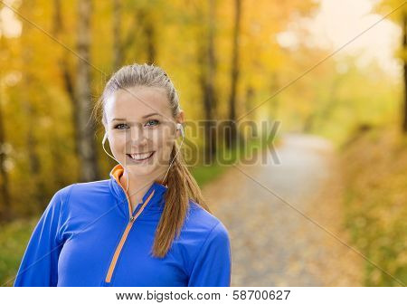 Sporty woman runner listens to music in nature