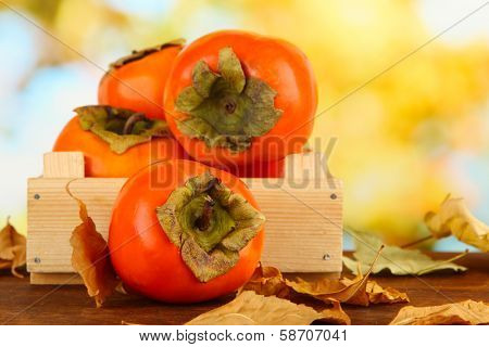 Ripe persimmons in crate on table on bright background