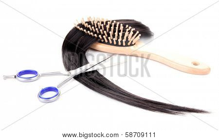 Long black hair with hairbrush and scissors isolated on white