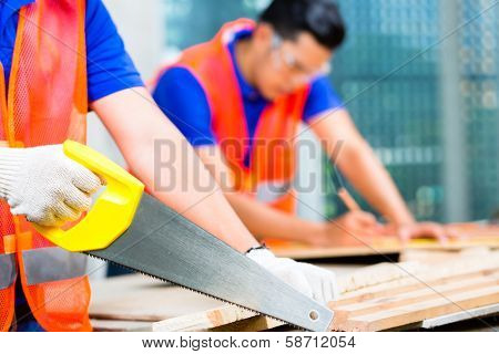 Asian Indonesian builder or craftsman sawing with a saw a wood board of a tower building or construction site wearing protection glasses and gloves