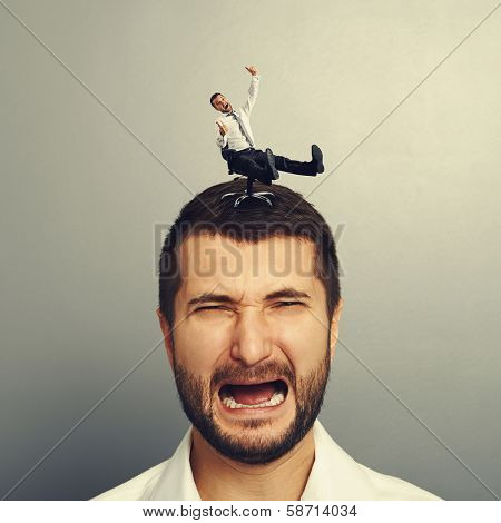 portrait of sad screaming man with small happy man on the head