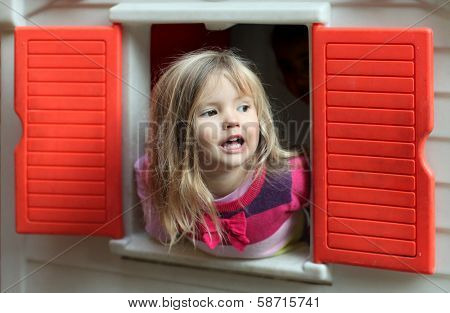Little blond girl looking through the window of kids playhouse