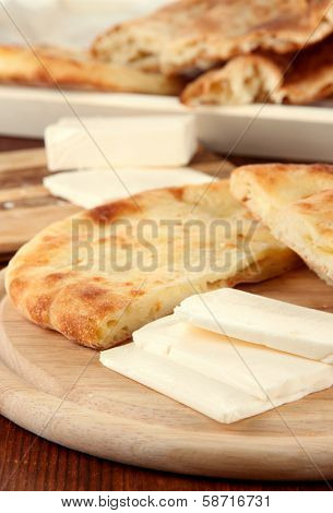 Pita breads with cheese on wooden stands close up