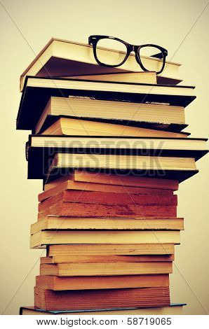 a pile of books and eyeglasses symbolizing the concept of reading habit or studying