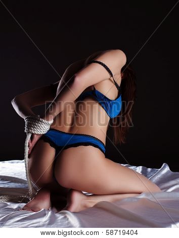 Rear view of seductive slim woman with tied hands