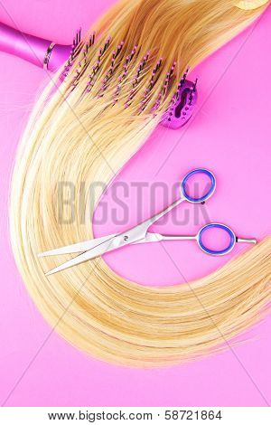 Long blond hair with hairbrush and scissors on pink background