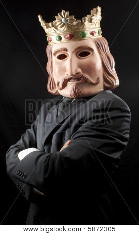 Businessman with king mask and crossed arms , isolated on black