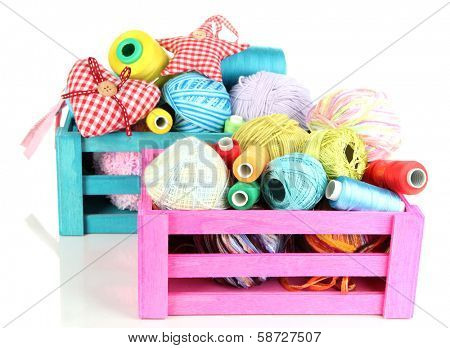 Wooden boxes with thread and sewing accessories isolated on white