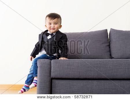 Little kid seating on sofa