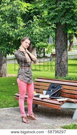 Young Woman Massaging Her Nape In A Park