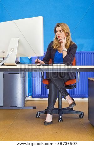 Young woman sitting behind a large screen in an office, working dilligently, showing signs of boredom due to repetitive work