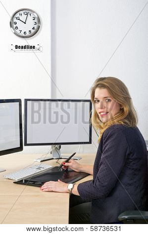 designer working towards a deadline, using a graphic tablet and a dual monitor computer. The clock on the wall symbolises the deadline