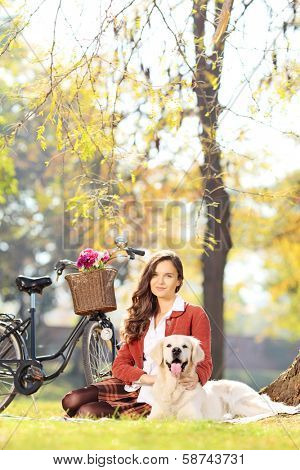 Beautiful female sitting on a green grass with her labrador retriever dog in a park, shot with a tilt and shift lens