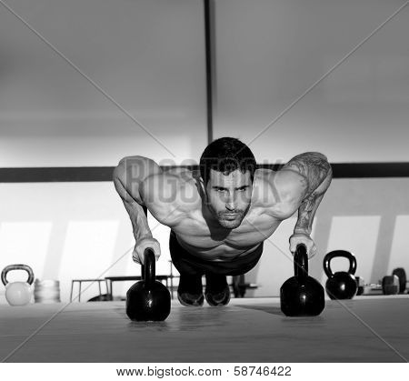 Gym man push-up strength pushup exercise with Kettlebell in a crossfit workout