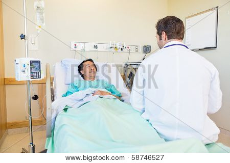 Smiling mature patient looking at doctor while lying on bed in hospital room