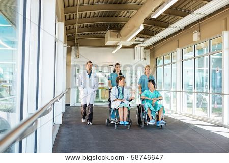 Nurses pushing patients on wheelchairs while walking with doctor at corridor in hospital
