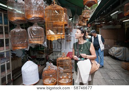 HONG KONG, CHINA - NOVEMBER 11, 2012: Tourists and locals in the bird market Bird Garden. Market is located on the Kowloon peninsula,  is one of the biggest and most popular bird markets in the world