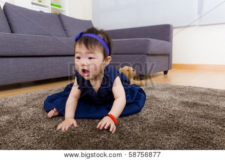 Baby girl creeping on carpet at home