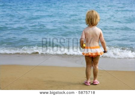 Blond Little Girl With Sandy Legs On The Beach