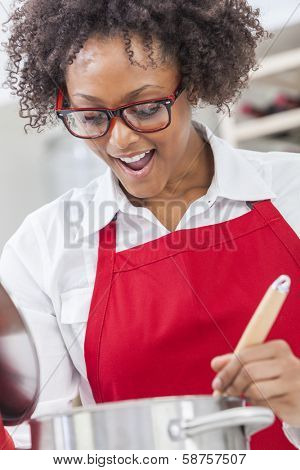 A beautiful mixed race African American girl or young woman looking happy wearing glasses a red apron & cooking in her kitchen at home