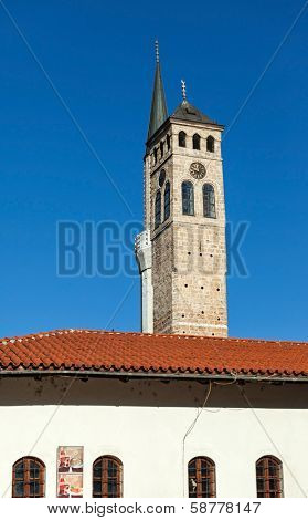 Sahat kula (Clock tower) and the The Gazi Husrev-bey Mosque Minaret against the blue sky.