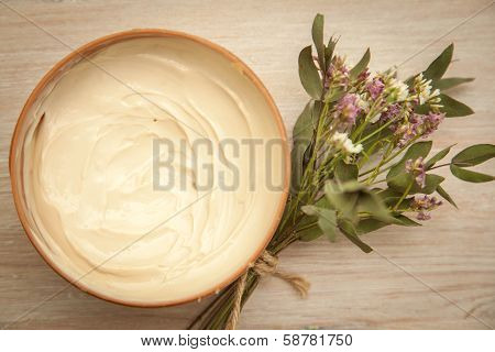 Body Cream And Wildflowers On Wooden Table