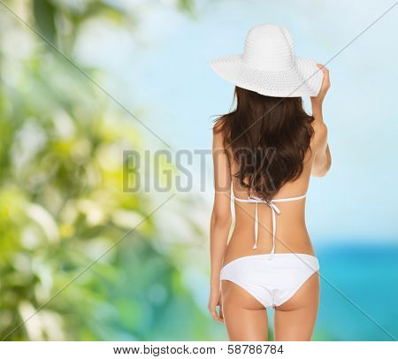 vacation, beauty and lingerie concept - back view of beautiful woman in white bikini and hat on a beach
