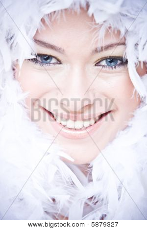 portrait of smiling young woman with white downy boa