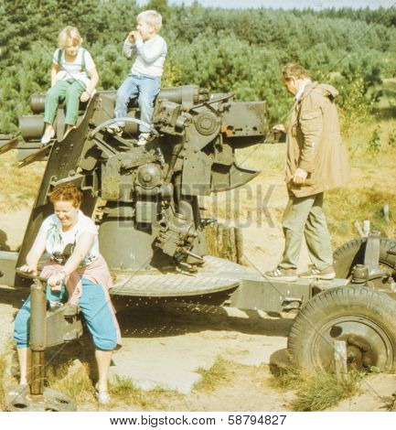 Vintage photo (scanned reversal film) of family visiting open air military museum, early eighties