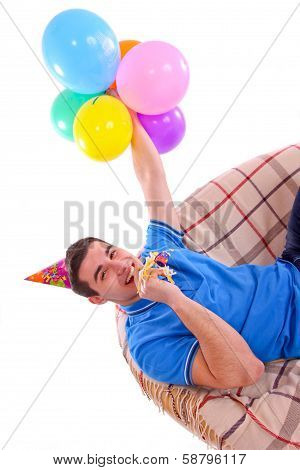 Guy sitting on the couch with a hat and balloons and whistling