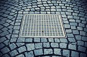 stock photo of manhole  - Paving stones background with metal manhole plate