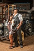 stock photo of mini-skirt  - Handsome muscular 1920s gangster with lady in mini skirt - JPG