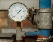 image of air pressure gauge  - Rusty Pressure Gauge connected to pipes with brick wall behind - JPG