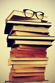 image of bookworm  - a pile of books and eyeglasses symbolizing the concept of reading habit or studying - JPG
