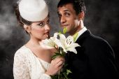 stock photo of mixed race  - bride and groom with flowers portrait studio shot - JPG