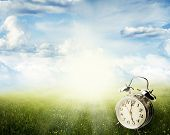 stock photo of daylight saving time  - Alarm clock in sunlit spring field - JPG
