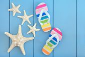 foto of beach shell art  - Starfish sea shells and rainbow coloured flip flops over wooden blue background - JPG
