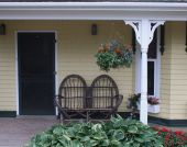 image of screen-porch  - Wicker chairs sit on the front porch - JPG