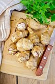 picture of jerusalem artichokes  - Whole tubers of Jerusalem artichoke with parsley knife napkin on the background of wooden boards