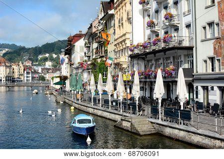 LUCERN, SWITZERLAND - JULY 2, 2014: Hotels and Restaurants on the River Reuss, Switzerland. The river is the fourth largest river in Switzerland and runs through Lake Lucern.