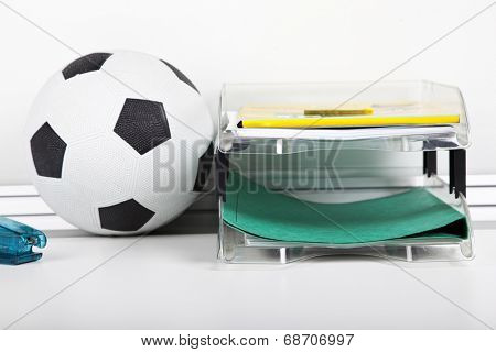Soccer ball near file rack at desk